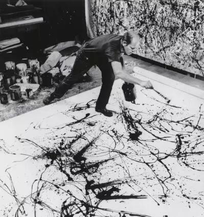 波洛克在用画笔或搅棒把颜料泼洒或滴到画布上