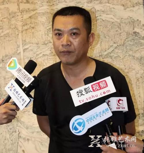 参展画家艾国接受记者采访