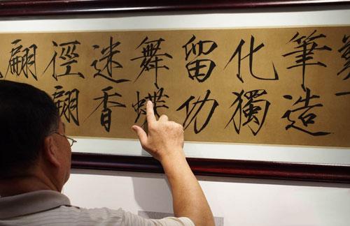 一位书法爱好者在墨宝瓷板上揣摩笔意