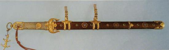 剑首依然为如意环形,中置手绳孔,孔周围装饰花纹,剑格已经从较为朴素