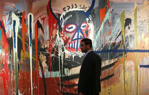佳士得的卢瓦克·古泽(Loïc Gouzer)站在2016年以5700万美元被藏家前泽友作买下的让·米歇尔·巴斯奎特(Jean-Michel Basquiat)画作。图片:KENABETANCUR/AFP/Getty Images