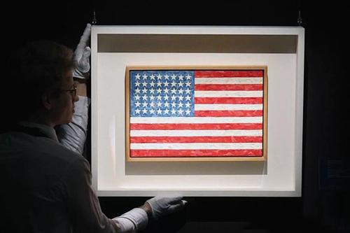 一名员工与Jasper Johns的旗帜作品合影。 摄影:Carl Court / Getty Images